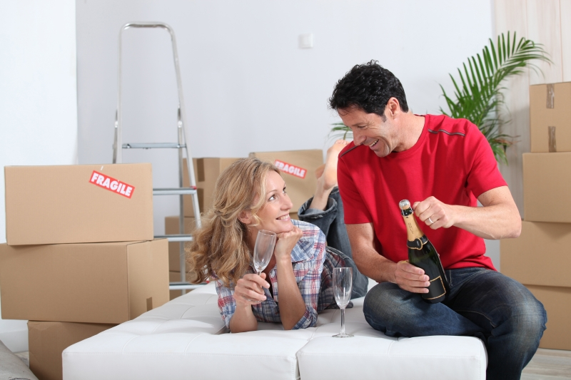 2744870-couple-lying-on-an-unmade-sofa-bed-celebrating-their-new-home-with-champagne